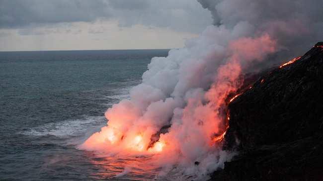 Manga de lava llegando al mar generando columna de humo
